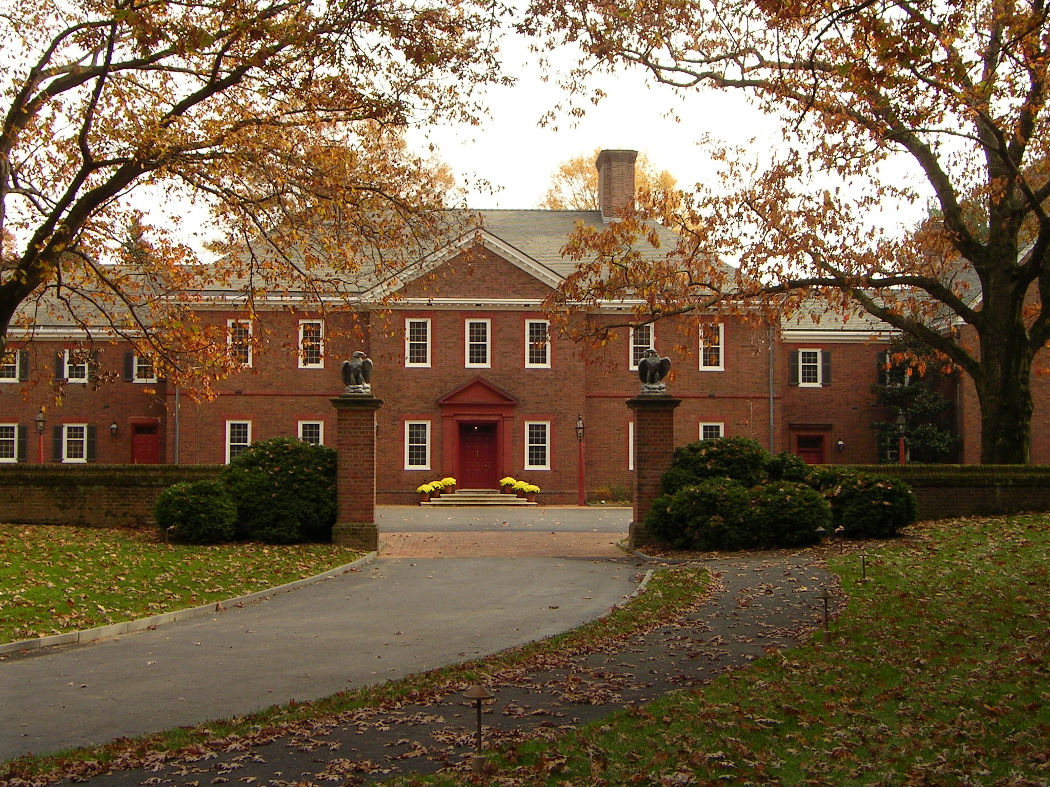 View of the Main House and Forecourt framed by two trees during autumn with leaf-covered paved pathways, steps leading up to the red Guest Entrance door, and red accessible entrance off to the left
