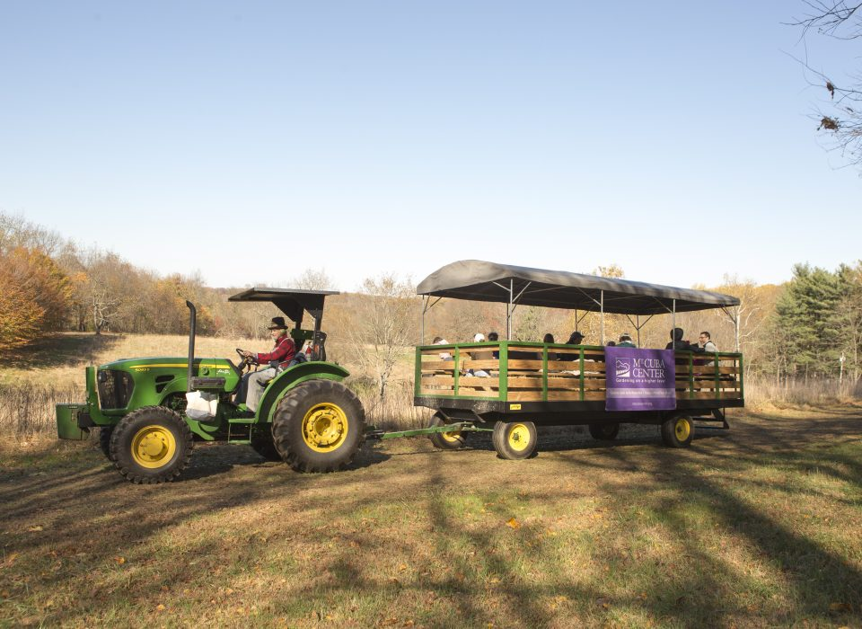 A tractor pulls a wagon of guests in the natural lands.