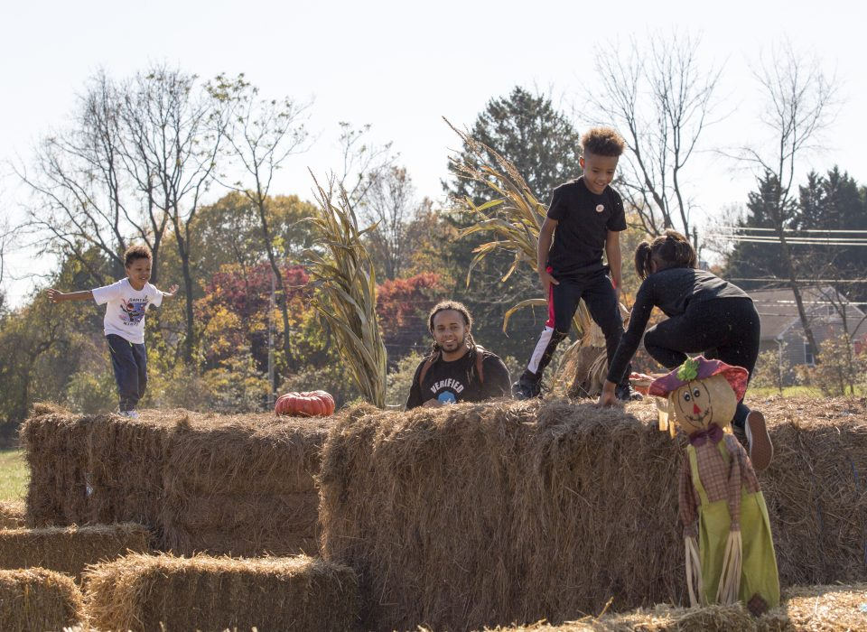 Picture of three children and one man playing on hay bales at Mt. Cuba Center