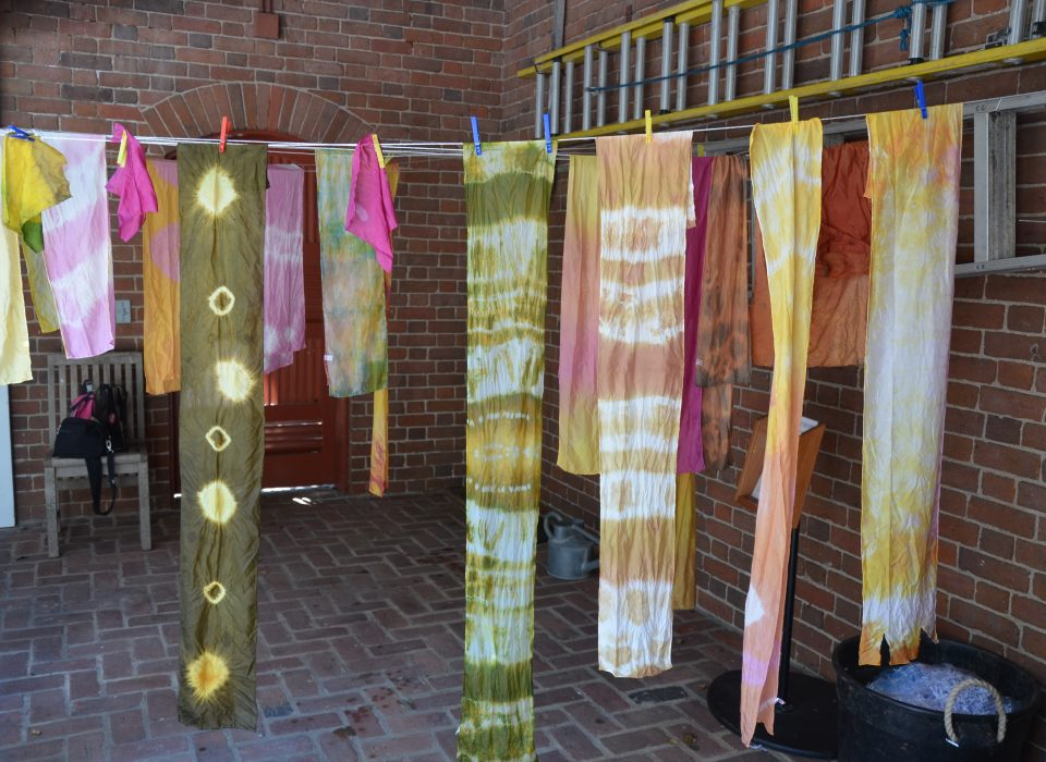 Colorful dyed pieces of fabric hang from line to dry.