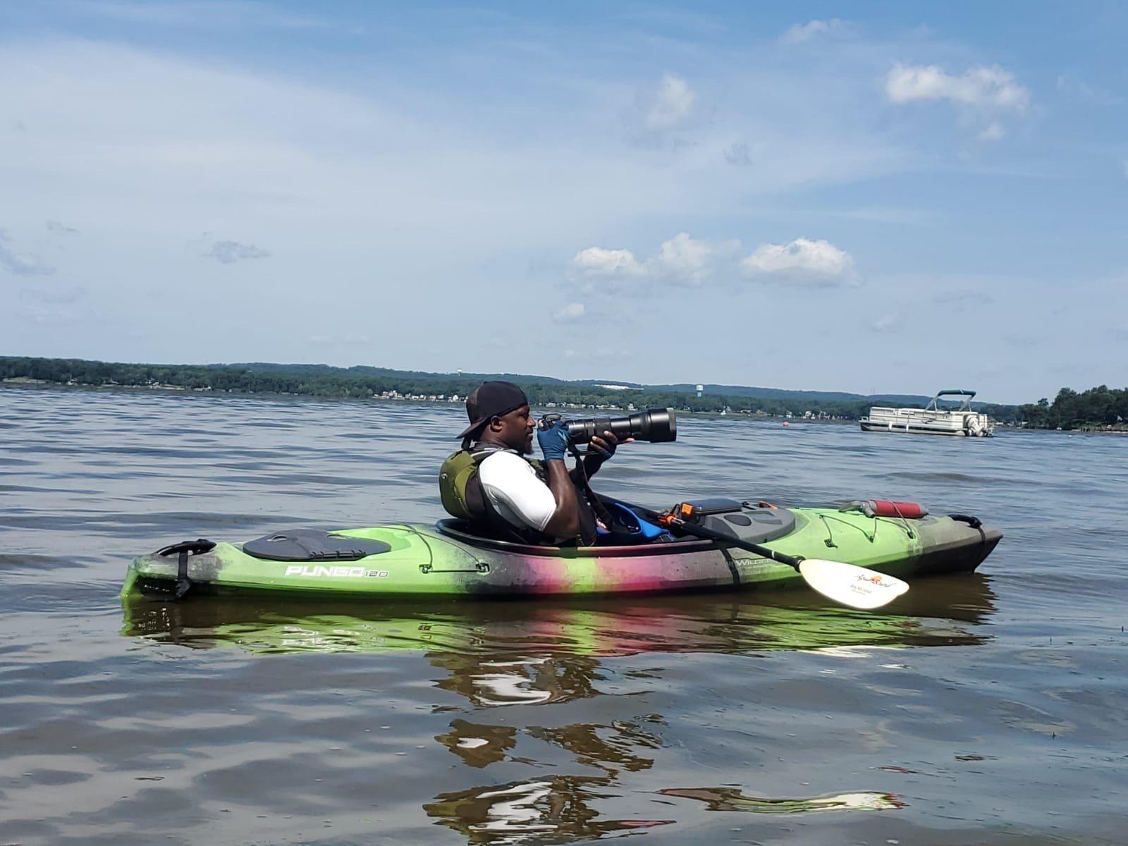 Professional nature photographer, David Greaves, taking photos in kayak on lake.